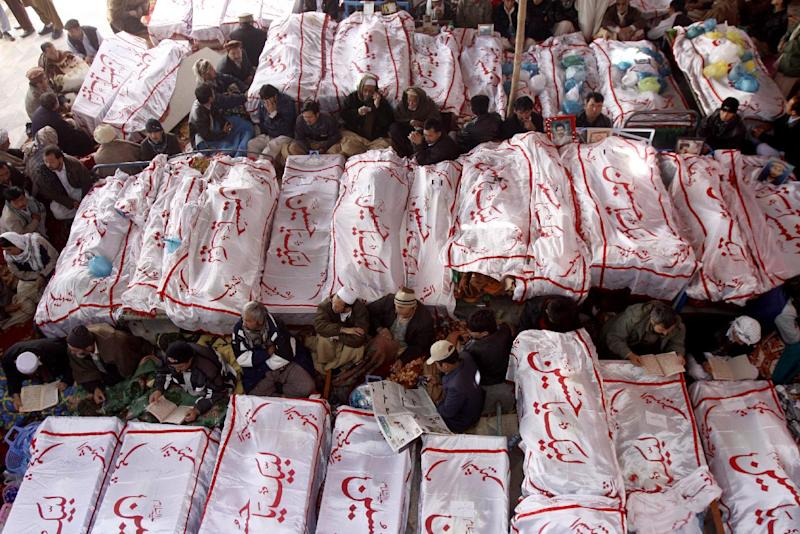 """Pakistani Shiite Muslims sit in protest next to the dead bodies of their family members killed in Saturday's bombing, in Quetta on Monday, Feb. 18, 2013. The protesters have refused to bury victims of the attack until authorities take action against the militants who were responsible. Writing on shrouds reads, """"We are ready Hussain."""" (AP Photo/Arshad Butt)"""