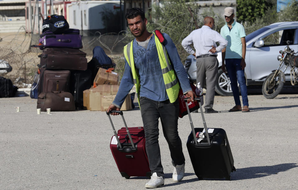 A worker pulls the luggage of passengers to a car in their way to cross the border to the Egyptian side of Rafah crossing, in Rafah, Gaza Strip, Tuesday, Aug. 11, 2020. Egypt reopened Rafah Crossing for three days starting Tuesday for humanitarian cases in and out of the Gaza Strip, including medical patients and people who had Egyptian and international citizenship. The border was closed since March. (AP Photo/Adel Hana)
