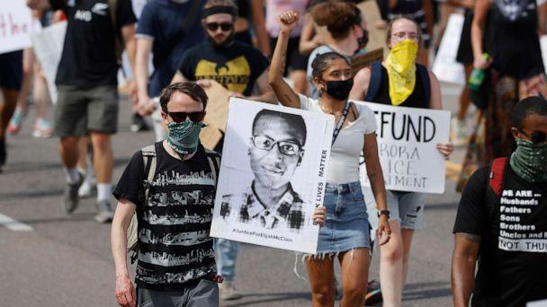 PHOTO: Demonstrators carry placards as they walk down Sable Boulevard during a rally and march over the death of 23-year-old Elijah McClain, June 27, 2020, in Aurora, Colo. (David Zalubowski/AP)