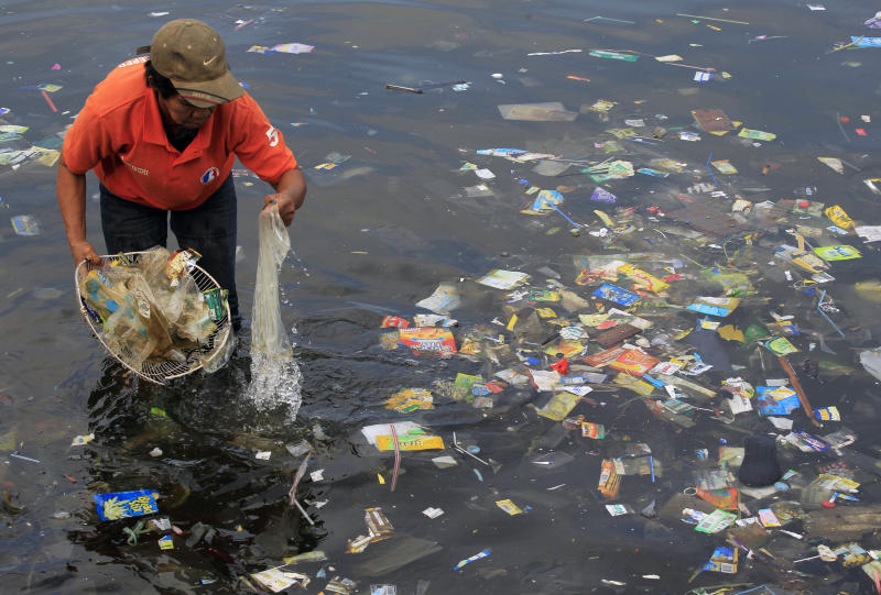 A government sanitary worker collects and segregate garbage, mostly assorted plastic products polluting in Manila Bay, Philippines. (Photo: Romeo Ranoco/Reuters)