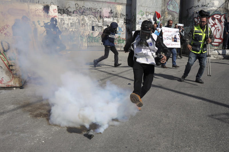 Palestinian photographer kicks away a sound bomb thrown by Israeli border police during a journalist's protest in support of a 35 year-old photographer Muath Amarneh in Bethlehem, West Bank, Sunday, Nov. 17, 2019. Amarneh's relatives say he has lost vision in one eye after apparently being struck by Israeli fire while covering a demonstration in the West Bank. Israel's paramilitary border police unit says it did not target him. (AP Photo/Mahmoud Illean)