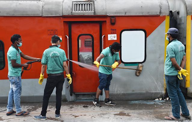 Workers wash and disinfect trains coaches at a rail yard, as a measure to prevent the spread of coronavirus in New Delhi.