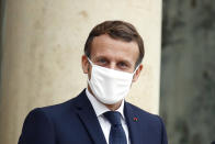France's President Emmanuel Macron wears a mask as he waits for Estonia's Prime Minister Juri Ratas, prior to a meeting at the Elysee Palace, in Paris, Wednesday, Oct. 28, 2020. France is bracing for a potential new lockdown as the president prepares a televised address Wednesday aimed at stopping a fast-rising tide of virus patients filling French hospitals and a growing daily death toll. French markets opened lower on expectations that President Emmanuel Macron will announce some kind of lockdown Wednesday. (AP Photo/Thibault Camus)