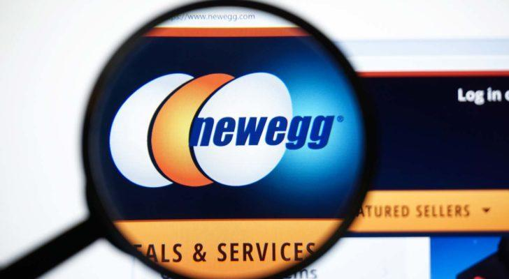 A magnifying glass zooms in on the website for Newegg (NEGG)