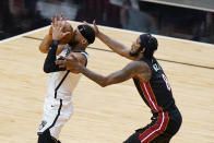 Brooklyn Nets guard Bruce Brown, left, loses control of the ball as he goes up for a shot against Miami Heat forward Trevor Ariza, right, during the second half of an NBA basketball game, Sunday, April 18, 2021, in Miami. (AP Photo/Wilfredo Lee)