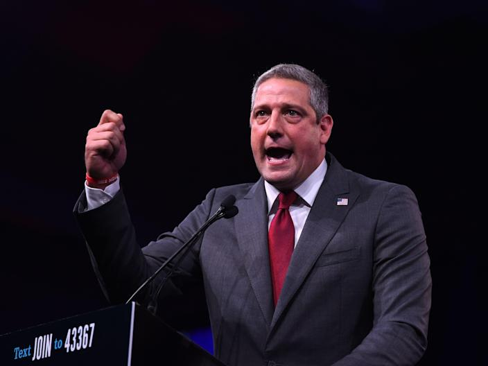Tim Ryan wears a gray suit and red tie as he delivers an impassioned speech