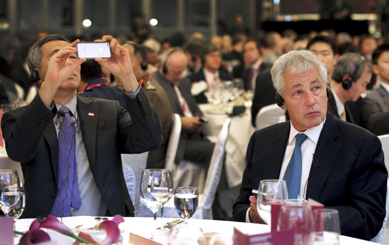 U.S. Secretary of Defense Chuck Hagel, right, listens to a keynote address while Singapore's Prime Minister Lee Hsien Loong snaps a photograph with his smartphone at the International Institute for Strategic Studies Shangri-la Dialogue, or IISS Asia Security Summit on Friday, May 31, 2013 in Singapore. The meetings will be held from May 31 to June 2. (AP Photo/Wong Maye-E)