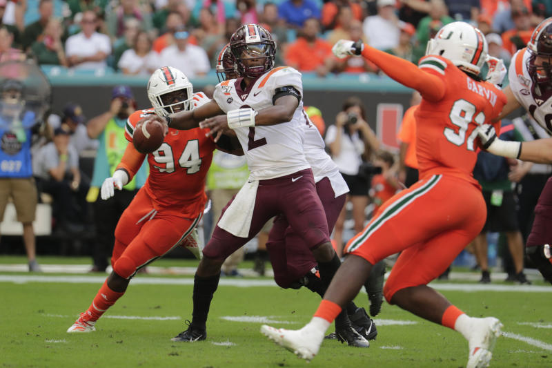 Virginia quarterback Hendon Hooker (2) stands back to pass as Miami defensive lineman Trevon Hill (94) and defensive lineman Jonathan Garvin (97) defend during the first half of an NCAA college football game, Saturday, Oct. 5, 2019, in Miami Gardens, Fla. (AP Photo/Lynne Sladky)