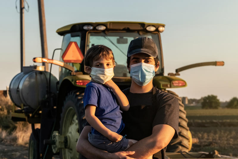 Young farmer posing with his son, both wearing protective face masks because COVID-19