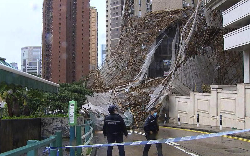 """In this image made from video provided by TVB, officials inspect the scene of a section of an apartment building scaffolding that collapsed during heavy weather in Hong Kong, Friday, Oct. 8, 2021. The official Hong Kong Observatory issued a Black Rainstorm Signal Friday, which indicates rainfall of more than 70 millimeters (2.76 inches) per hour all over the territory, and instructed people to """"stay indoors or take shelter in a safe place"""". (TVB via AP Video)"""