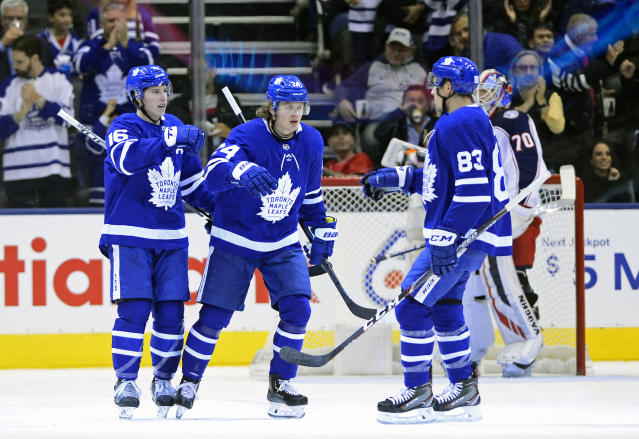Toronto Maple Leafs right wing Kasperi Kapanen, center, celebrates his goal against the Columbus Blue Jackets with teammates Mitchell Marner, left, and Cody Ceci during first-period NHL hockey game action in Toronto, Monday, Oct. 21, 2019. (Frank Gunn/The Canadian Press via AP)