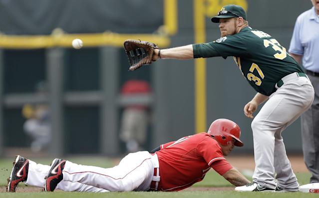 Cincinnati Reds' Shin-Soo Choo, of South Korea, dives safely back to first base as Oakland Athletics first baseman Brandon Moss (37) catches the late pickoff throw from starting pitcher Bartolo Colon during the first inning of a baseball game, Wednesday, Aug. 7, 2013, in Cincinnati. (AP Photo/Al Behrman)