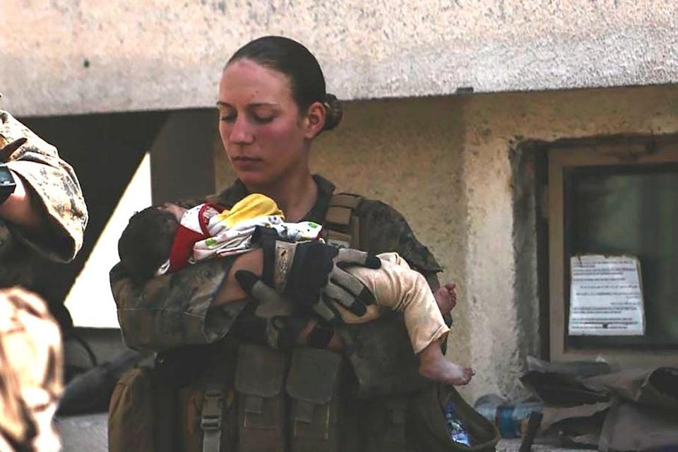 Sgt. Nicole Gee holding a baby at Hamid Karzai International Airport in Kabul, Afghanistan. She was killed Thursday's blast  (AP)