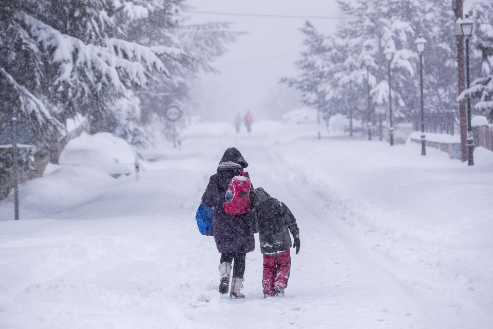 People walk under a heavy snowfall in Bustarviejo, outskirts of Madrid, Spain, Saturday, Jan. 9, 2021. A persistent blizzard has blanketed large parts of Spain with 50-year record levels of snow, halting traffic and leaving thousands trapped in cars or in train stations and airports that suspended all services as the snow kept falling on Saturday. Half of Spain is on alert, with five provinces on their highest level of warning. (AP Photo/Bernat Armangue)