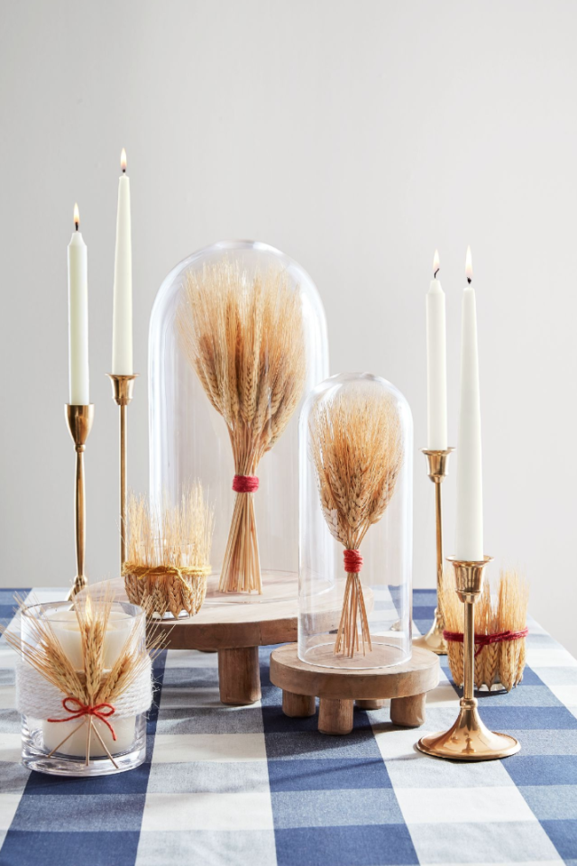 """<p>If you're looking for a sophisticated farmhouse feel, these DIY wheat cloches are refined <em>and </em>natural touches.</p><p><strong>Assemble the Cloches: </strong>Bundle a <a href=""""https://www.amazon.com/BD-Crafts-Natural-dried-sheaves/dp/B072KZHWXJ"""" target=""""_blank"""">small handful of wheat</a> and tie with <a href=""""https://www.amazon.com/Vivifying-Natural-Crafts-Wrapping-Garden/dp/B07G54KP8D"""" target=""""_blank"""">twine</a>. Turn a <a href=""""https://www.amazon.com/Lights4fun-Inc-Cloche-Display-Bamboo/dp/B012SXD1XE"""" target=""""_blank"""">cloche</a> upside down and place the wheat inside, then top with base and invert. Add leftover snips of wheat to votive holders (securing with twine).<a href=""""https://www.amazon.com/Lights4fun-Inc-Cloche-Display-Bamboo/dp/B012SXD1XE"""" target=""""_blank""""></a></p><p><a class=""""body-btn-link"""" href=""""https://www.amazon.com/Lights4fun-Inc-Cloche-Display-Bamboo/dp/B012SXD1XE?tag=syn-yahoo-20&ascsubtag=%5Bartid%7C10050.g.2063%5Bsrc%7Cyahoo-us"""" target=""""_blank"""">SHOP GLASS CLOCHES</a></p>"""