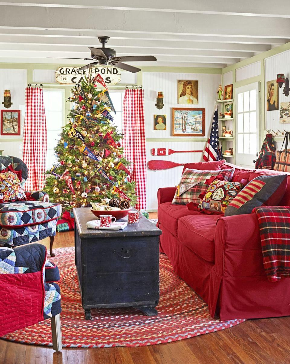 """<p>The owner of <a href=""""https://www.countryliving.com/home-design/house-tours/g3857/christmas-camp-decorating-ideas/"""" rel=""""nofollow noopener"""" target=""""_blank"""" data-ylk=""""slk:this California cabin"""" class=""""link rapid-noclick-resp"""">this California cabin</a> uses red year-round as an ode to the words of Charles Dickens: """"I will honor Christmas in my heart, and try to keep it all the year."""" The tree is peppered with pennants from National Parks and roadside attractions.</p><p><strong><a class=""""link rapid-noclick-resp"""" href=""""https://www.amazon.com/Achim-Home-Furnishings-Buffalo-Burgundy/dp/B005L8ZNK8?tag=syn-yahoo-20&ascsubtag=%5Bartid%7C10050.g.1247%5Bsrc%7Cyahoo-us"""" rel=""""nofollow noopener"""" target=""""_blank"""" data-ylk=""""slk:SHOP CURTAINS"""">SHOP CURTAINS</a></strong></p>"""