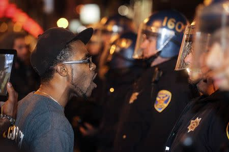 A protester yells at a line of police officers during a demonstration against the grand jury decision in the Ferguson, Missouri shooting of Michael Brown in San Francisco, California November 28, 2014. REUTERS/Elijah Nouvelage