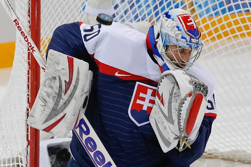 A shot on goal flies by Slovakia goaltender Jan Laco during the first period of the 2014 Winter Olympics men's ice hockey game against the Czech Republic at Shayba Arena, Tuesday, Feb. 18, 2014, in Sochi, Russia. (AP Photo/Petr David Josek)