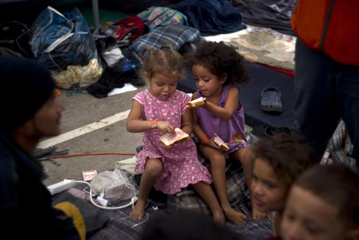 Two girls, part of the migrant caravan, share a sandwich at a shelter in Tijuana, Mexico, Wednesday, Nov. 21, 2018. Migrants camped in Tijuana after traveling in a caravan to reach the U.S are weighing their options after a U.S. court blocked President Donald Trump's asylum ban for illegal border crossers. (AP Photo/Ramon Espinosa)