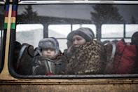 A displaced woman and a young boy sit in a bus before fleeing the Ukrainian city of Debaltseve, in the Donetsk region, on February 1, 2015 (AFP Photo/Manu Brabo)