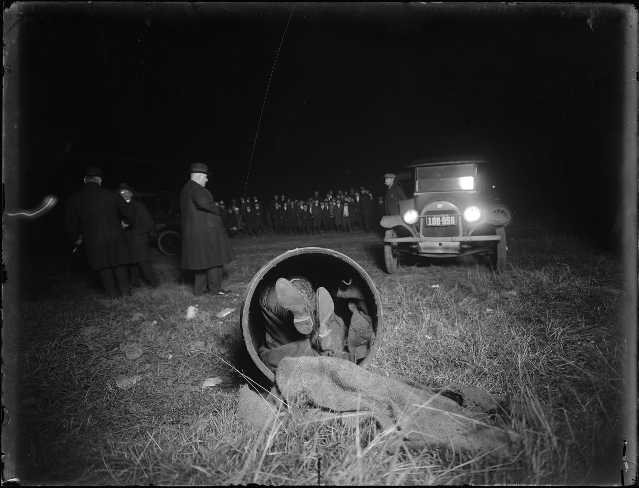 In this 1918 photo provided by the New York City Municipal Archives, police work a homicide after children found the body of Gaspare Candella stuffed in a burlap covered drum out in the middle of a Brooklyn, N.Y. field. Over 870,000 photos from an archive that exceeds 2.2 million images have been scanned and made available online, for the first time giving a global audience a view of a rich collection that documents life and sometimes death in New York City.  (AP Photo/New York City Municipal Archives, NYPD Evidence Collection, Detective Charles A. Carlstrom) MANDATORY CREDIT
