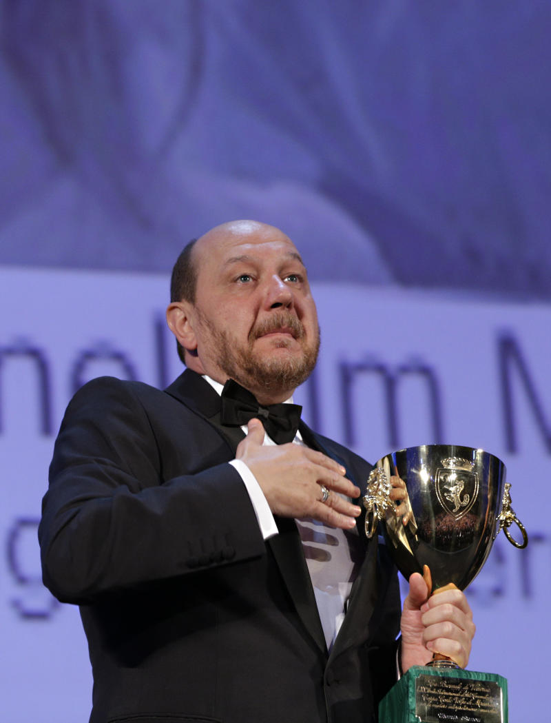Actor Themis Panou holds his Volpi Cup for Best Actor for his role in the film Miss Violence, during the awards ceremony of the 70th edition of the Venice Film Festival in Venice, Italy, Saturday, Sept. 7, 2013. (AP Photo/Domenico Stinellis)