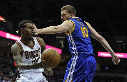 Milwaukee Bucks' Brandon Jennings (3) looks to pass as he is hit in the face by Golden State Warriors' David Lee (10) during the second half of an NBA basketball game on Saturday, Jan. 26, 2013, in Milwaukee. The Bucks defeated the Warriors 109-102. (AP Photo/Jim Prisching)