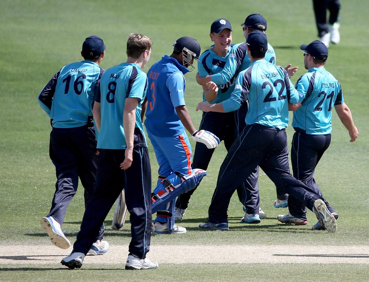 DUBAI, UNITED ARAB EMIRATES - FEBRUARY 17:  Players of Scotland celebrate the wicket of Ricky Bhui of India during the ICC U19 Cricket World Cup 2014 match between India and Scotland at the Dubai Sports City Cricket Stadium on February 17, 2014 in Dubai, United Arab Emirates.  (Photo by Francois Nel - IDI/IDI via Getty Images)