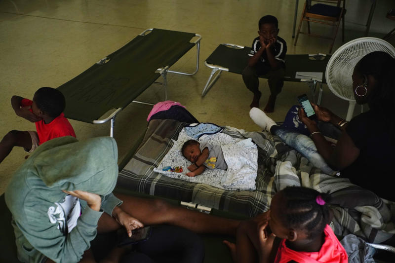 Anastacia Makey, 43, far right, looks at her phone as she and her family sits on cots with other residents inside a church that was opened up as a shelter as they wait out Hurricane Dorian in Freeport on Grand Bahama, Bahamas, Sunday, Sept. 1, 2019. Hurricane Dorian intensified yet again Sunday as it closed in on the northern Bahamas, threatening to batter islands with Category 5-strength winds, pounding waves and torrential rain. (AP Photo/Ramon Espinosa)