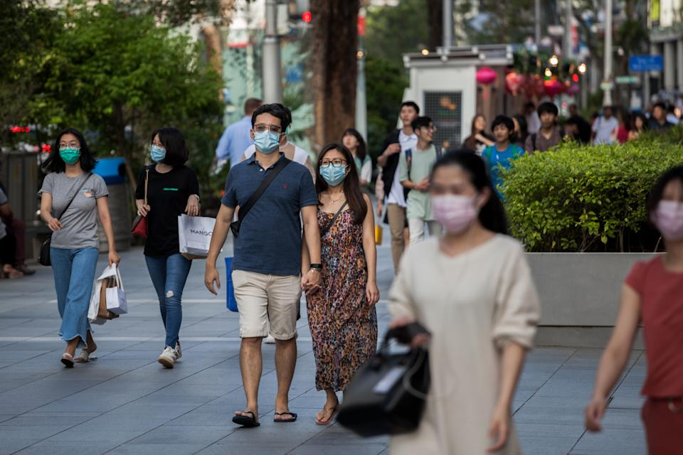 People wearing protective face masks walks along Orchard Road on 14 February, 2020. (PHOTO: LightRocket via Getty Images)