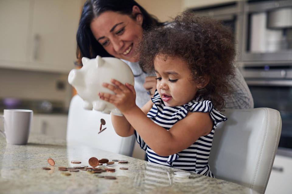 Mother and toddler girl getting money out of a piggy bank