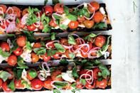 """How do you improve on a classic Caprese salad? Grill your tomatoes—and then spill them over charred baguette. There's no balsamic vinegar in this recipe—instead, the mix of tomato and mozzarella is brightened with shallots that sit for a moment in a bit of red wine vinegar. Serve with a <a href=""""https://www.epicurious.com/recipes/food/views/aperol-spritz?mbid=synd_yahoo_rss"""" rel=""""nofollow noopener"""" target=""""_blank"""" data-ylk=""""slk:spritz"""" class=""""link rapid-noclick-resp"""">spritz</a> and a platter of prosciutto or antipasto on the side for an Italian-themed happy hour. <a href=""""https://www.epicurious.com/recipes/food/views/charred-caprese-sandwich?mbid=synd_yahoo_rss"""" rel=""""nofollow noopener"""" target=""""_blank"""" data-ylk=""""slk:See recipe."""" class=""""link rapid-noclick-resp"""">See recipe.</a>"""