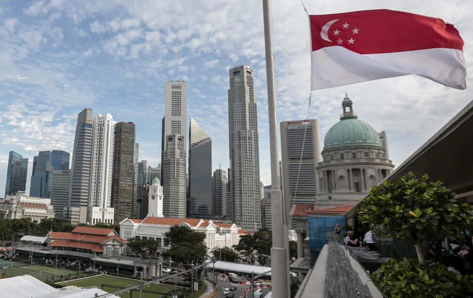 The flag of Singapore flies with city skyscrapers in the background.