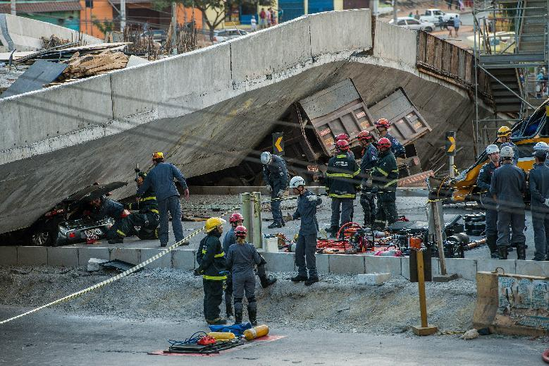 Firefighters and policemen work at the site where several vehicles were crushed by a viaduct that collapsed in Belo Horizonte, Brazil, on July 3, 2014