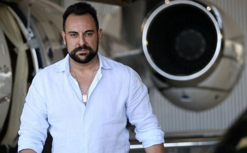 Entrepreneur Sam Bashiry standing in front of a parked airplane.