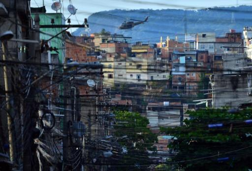 A police helicopter overflies the Favela da Mare shantytown complex in Rio de Janeiro in March 2014 -- the use of helicopters in police raids has increased in recent months