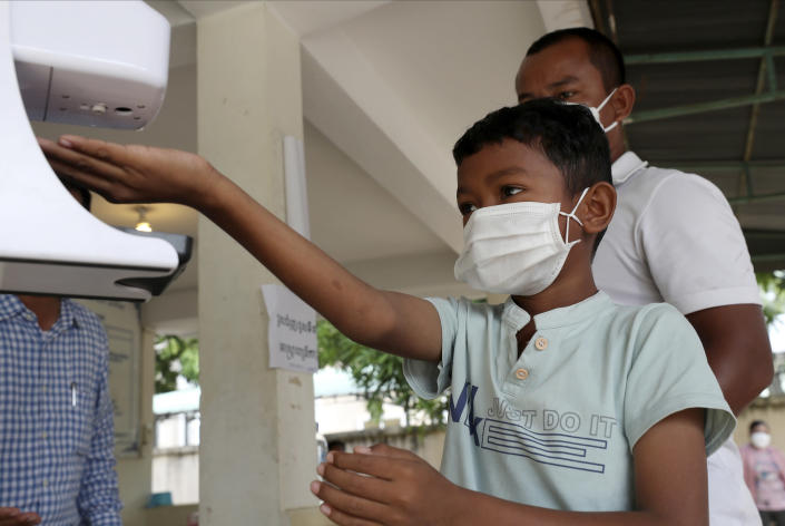 A young boy, left, disinfects his hands before receiving a shot of the Sinovac's COVID-19 vaccine at Samrong Krom health center outside Phnom Penh, Cambodia, Friday, Sept. 17, 2021. Prime Minister Hun Sen announced the start of a nationwide campaign to give COVID-19 vaccinations to children between the ages of 6 and 11 so they can return to school safely after a long absence due to measures taken against the spread of the coronavirus. (AP Photo/Heng Sinith)