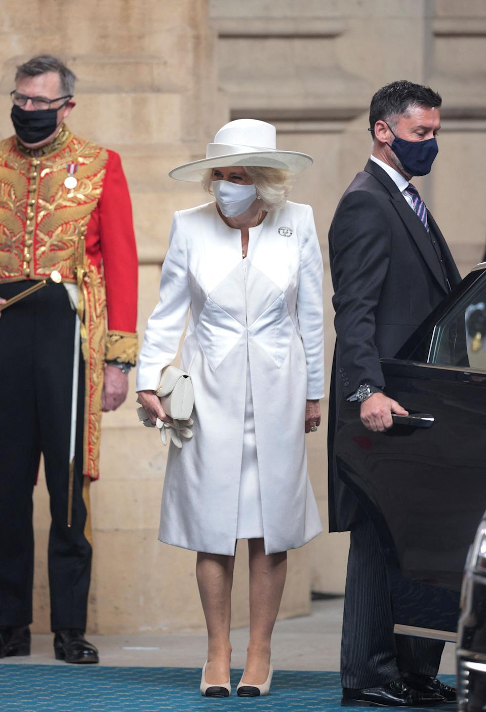 Britain's Camilla, Duchess of Cornwall (C), wearing a face covering,  arrives for the State Opening of Parliament at the Houses of Parliament in London on May 11, 2021, which is taking place with a reduced capacity due to Covid-19 restrictions. - The State Opening of Parliament is where Queen Elizabeth II performs her ceremonial duty of informing parliament about the government's agenda for the coming year in a Queen's Speech. (Photo by HANNAH MCKAY / POOL / AFP) (Photo by HANNAH MCKAY/POOL/AFP via Getty Images)