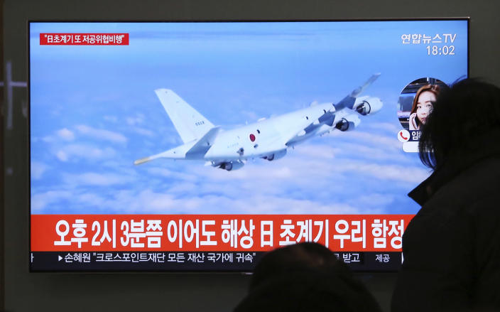 """People watch a TV screen showing file footage of a Japanese patrol plane during a news program at the Seoul Railway Station in Seoul, South Korea, Wednesday, Jan. 23, 2019. South Korea's military accused Japan of a """"clear provocation"""" over what it said was a threatening low-altitude flight by a Japanese patrol plane over a South Korean warship on Wednesday. The Korean letters on the screen read: """"At 2:03 p.m., a Japanese patrol plane flew close to a South Korea's warship."""" (AP Photo/Ahn Young-joon)"""
