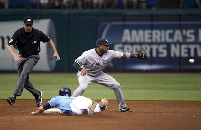 Tampa Bay Rays' Matt Joyce slides safely for a double as New York Yankees second baseman Robinson Cano, right, waits for the throw from the outfield in the sixth inning of a baseball game in St. Petersburg, Fla., Sunday, Aug. 25, 2013. Watching is second base umpire Gary Darling. (AP Photo/Phelan M. Ebenhack)