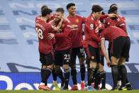 Manchester United's Luke Shaw celebrates with Bruno Fernandes, left, after scoring his side's second goal during the English Premier League soccer match between Manchester City and Manchester United at the Etihad Stadium in Manchester, England, Sunday, March 7, 2021. (Peter Powell/Pool via AP)