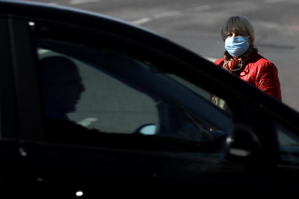 A woman wearing a face mask to protect against the coronavirus, waits to cross a road in London, Tuesday, May 12, 2020, as the country continues in lockdown. Advice from the government is now to wear face covering when entering enclosed spaces such as shops. (AP Photo/Kirsty Wigglesworth)