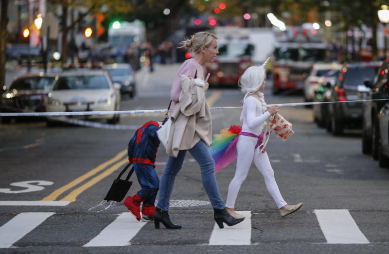 Kids in Halloween costumes cross the street near the scene where eight people were killed earlier in the day in a suspected terrorist attack in lower Manhattan. (Kena Betancur via Getty Images)