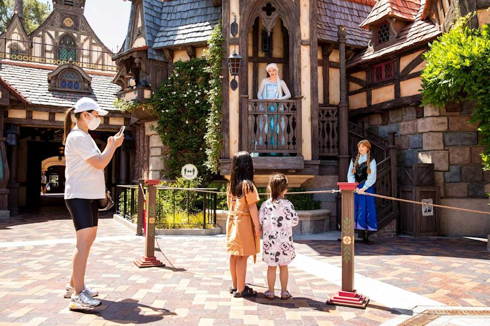 A family takes pictures and has socially distant interaction with Elsa and Anna characters at Disneyland Resort in Anaheim, CA.