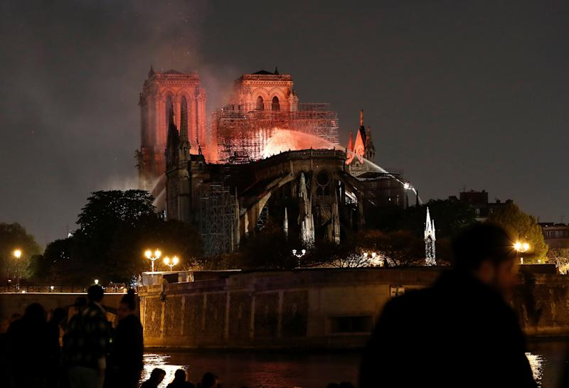 Firefighters douse flames from the burning Notre Dame Cathedral as people look on in Paris, France April 15, 2019. REUTERS/Benoit Tessier