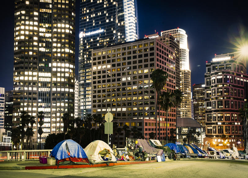 Los Angeles, CA, USA - September 2018: View of homeless people tents near the highway in LA Downtown with skyscrapers.