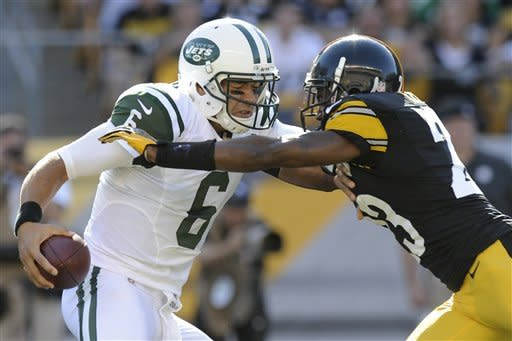 New York Jets quarterback Mark Sanchez (6) is pressured by Pittsburgh Steelers cornerback Keenan Lewis (23) before twisting away to throw a pass in the first quarter of an NFL football game on Sunday, Sept. 16, 2012, in Pittsburgh. (AP Photo/Don Wright)