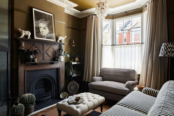 """AFTER: For their """"adult"""" living room. The couple opted for a split-level paint scheme with limewash paint on top to avoid accidental (and hard-to-restore) smudges by playing children. Most of the furniture came from their previous house and was reupholstered with bold-patterned fabrics, while the fireplace is a vintage find."""