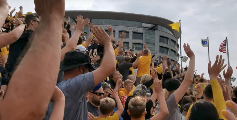 Iowa football crowd stands to wave at children in neighboring hospital