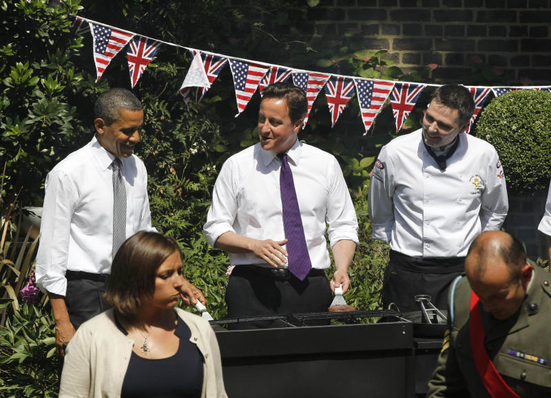 U.S. President Barack Obama, left, and British Prime Minister David Cameron, center, work the grill as they visit with British and American service members and veterans at a barbeque at 10 Downing Street in London, Wednesday, May 25, 2011. (AP Photo/Charles Dharapak)